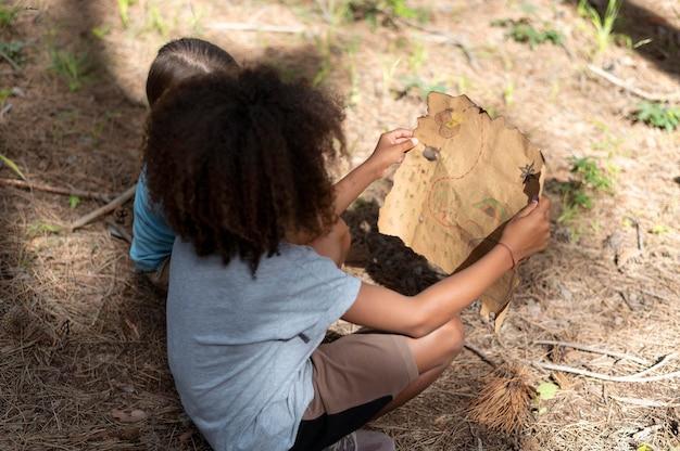 Crianças participando de uma caça ao tesouro em uma floresta