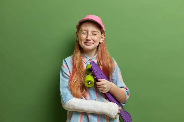 Crianças, passatempo perigoso e conceito de lesões. garota ruiva satisfeita fecha os olhos e se sente feliz, segura o skate debaixo do braço, teve trauma durante o skate, tem descanso de verão ativo, isolado no verde