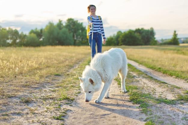 Crianças passeando com cachorro branco em um prado no dia de outono