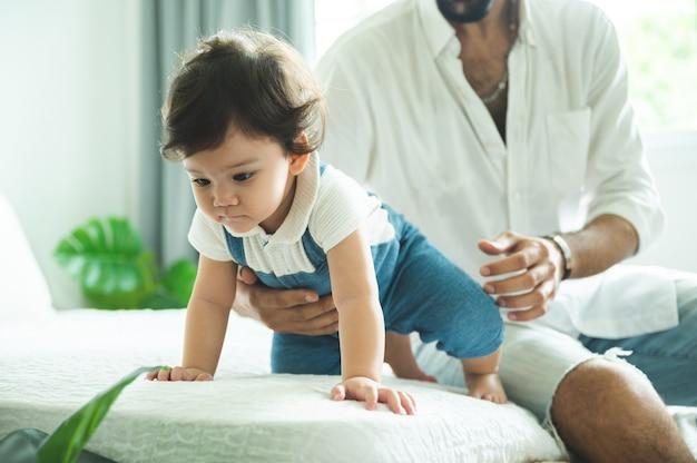 Crianças pequenas com primeiro passo de caminhada com escadas em casa, bebês pequenos ficam felizes em brincar e aprender a engatinhar com a família, lindo menino se divertindo e cuidando da infância
