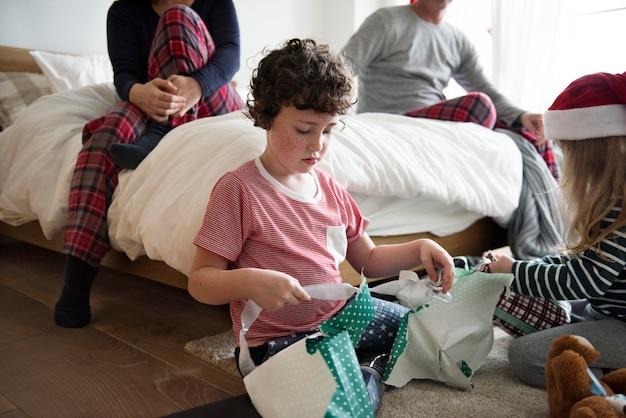 Crianças pequenas desembrulhando presentes de natal