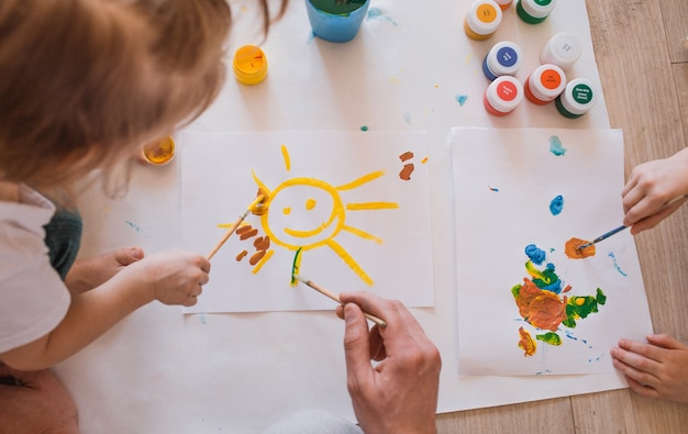 Crianças pequenas desenham no chão com aquarela vista de cima. o desenvolvimento da arte em crianças
