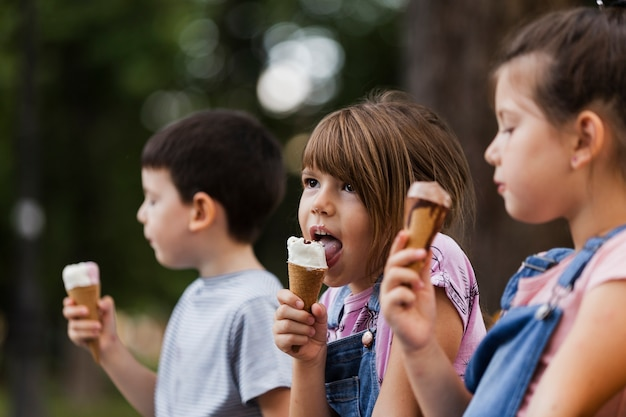 Crianças pequenas, desfrutando de sorvete ao ar livre