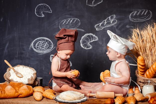 Crianças pequenas encantadoras de aventais na mesa com pão