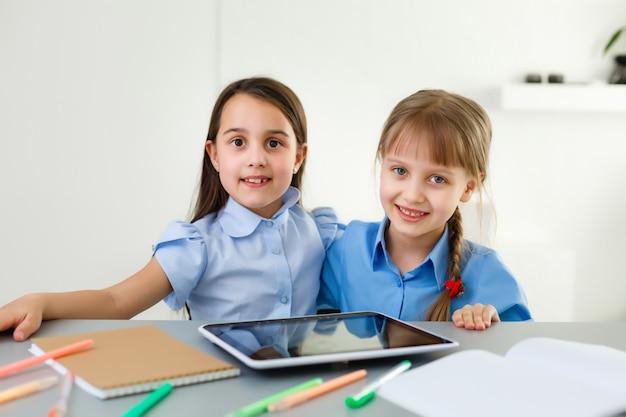 Crianças pequenas estudam aprendizagem on-line em casa com laptop e tablet