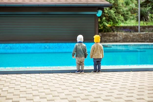 Crianças pequenas ficam perto de uma piscina funda sem supervisão de um adulto
