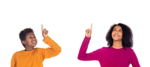 Crianças pequenas indicando algo com o dedo isolado em um branco