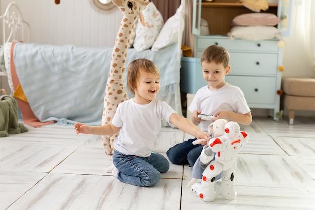 Crianças pequenas, irmão e irmã, sentam-se no chão da sala, rindo e brincando com o robô