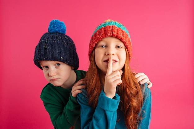 Crianças pequenas isoladas mostrando o gesto do silêncio.