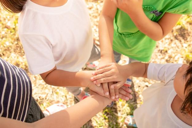 Crianças pequenas juntando as mãos dentro de casa, vista superior.