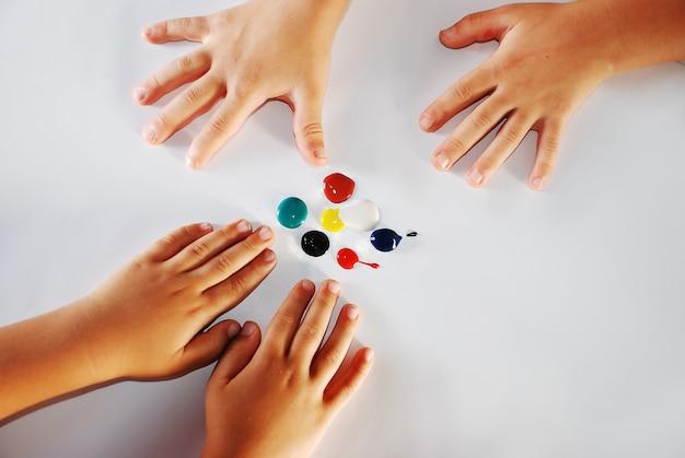 Crianças pequenas mãos brincando com as cores no fundo branco