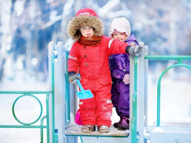 Crianças pequenas na roupa do inverno que tem o divertimento no campo de jogos no dia de inverno nevado. as crianças brincam ao ar livre. ativo ao ar livre para férias em família