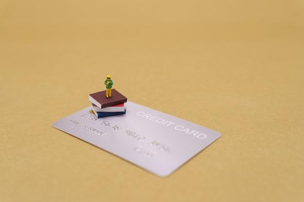 Crianças pequenas pessoas em miniatura no modelo de cartões de crédito usando como plano de fundo o conceito de educação