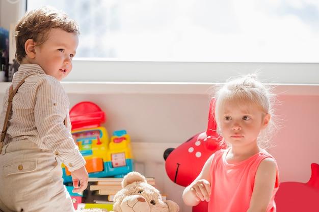 Crianças pequenas posando na janela