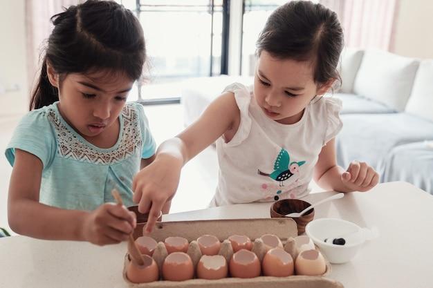 Crianças pequenas que plantam mudas em cascas de ovos reutilizadas, educação escolar em casa montessori
