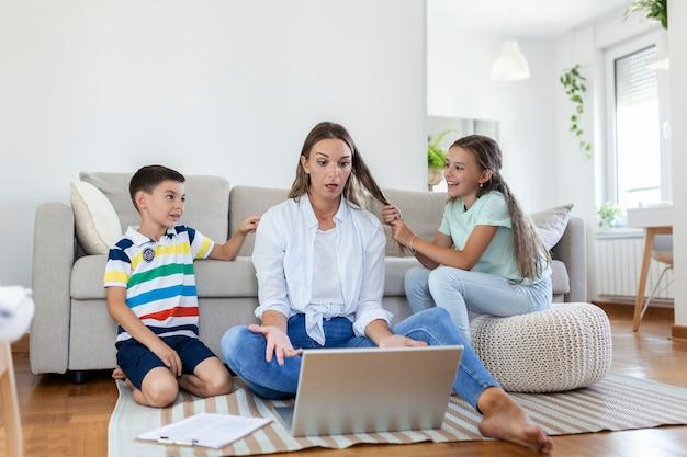Crianças pequenas travessas fazendo barulho e distraindo a mãe freelancer tentando se concentrar no laptop e apertando a cabeça trabalhando na mesa em uma sala iluminada