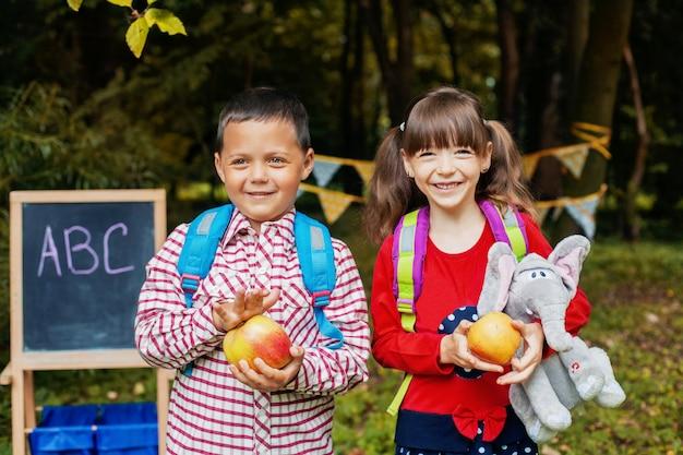 Crianças pequenas vão à escola com mochilas. de volta à escola. educação, escola, infância