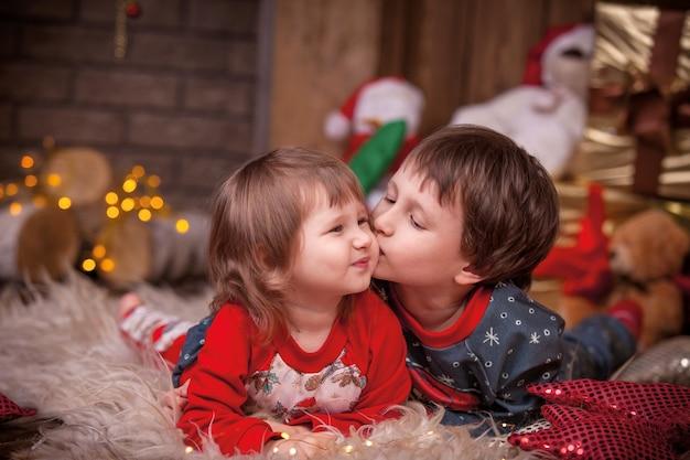 Crianças perto da árvore de natal com presentes
