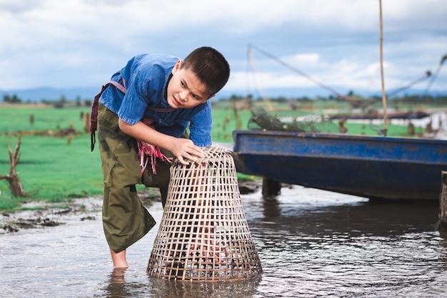 Crianças pescando e se divertindo no canal. estilo de vida das crianças na zona rural da tailândia.