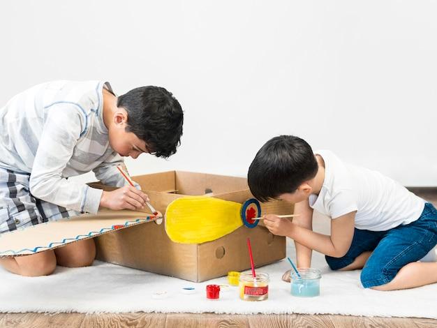 Crianças pintando barco de papelão