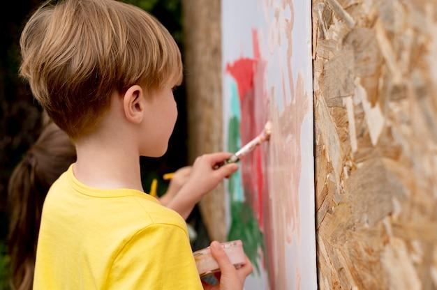 Crianças pintando com pincéis de perto