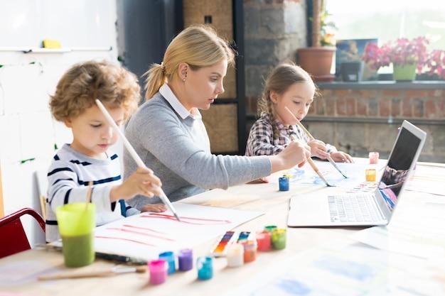 Crianças pintando com professor