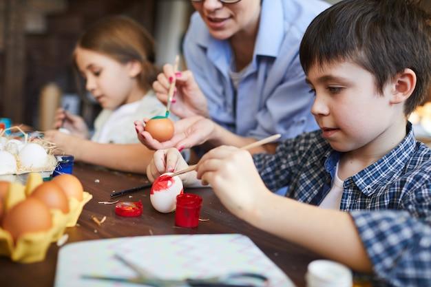 Crianças pintando ovos de páscoa