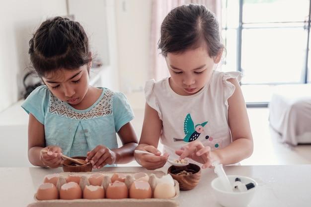 Crianças plantando mudas em cascas de ovos de reutilização, educação homeschool montessori