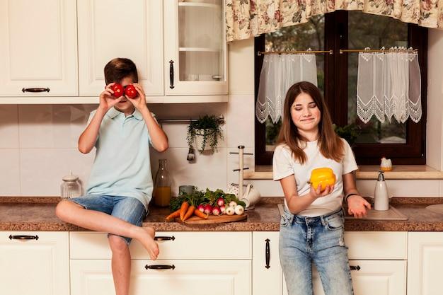 Crianças posando com legumes na cozinha
