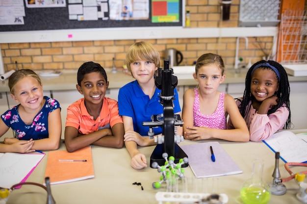 Crianças posando com microscópio