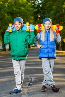 Crianças posando com skate ao ar livre