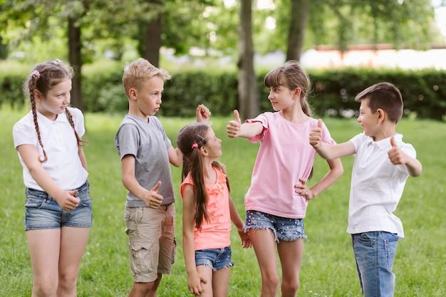 Crianças posando e fazendo o sinal de ok
