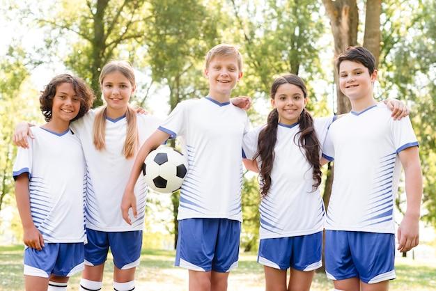 Crianças posando juntas em equipamentos de futebol