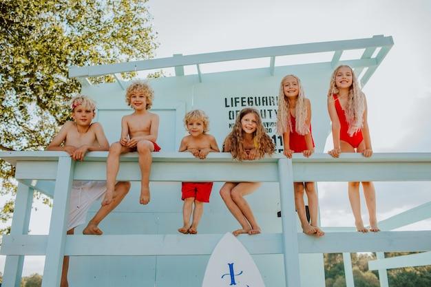 Crianças posando na praia de areia com a torre do salva-vidas e a felicidade da prancha de surfe