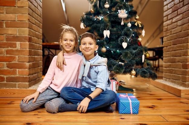 Crianças posando para árvore de natal