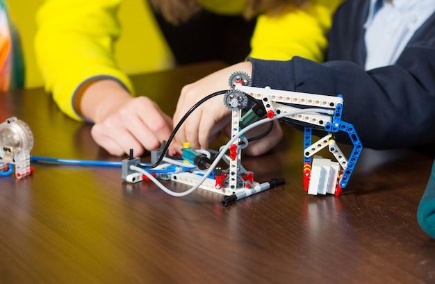 Crianças positivas brincam e montam o construtor no quarto das crianças.