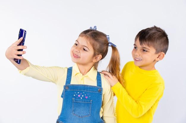 Crianças pré-escolares estão sorrindo e posando enquanto tomam selfie em um smartphone.