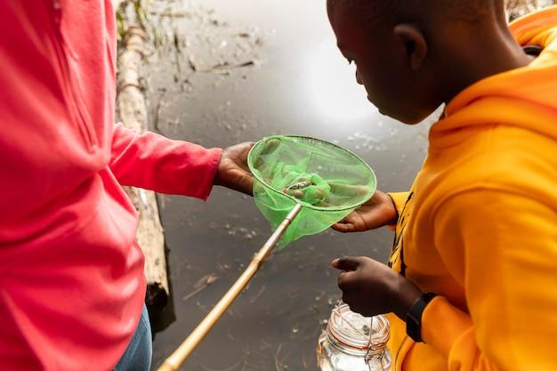Crianças procurando em uma ferramenta de pesca