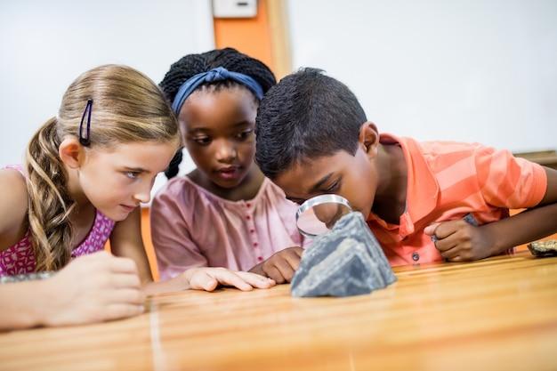 Crianças procurando fósseis com uma lupa
