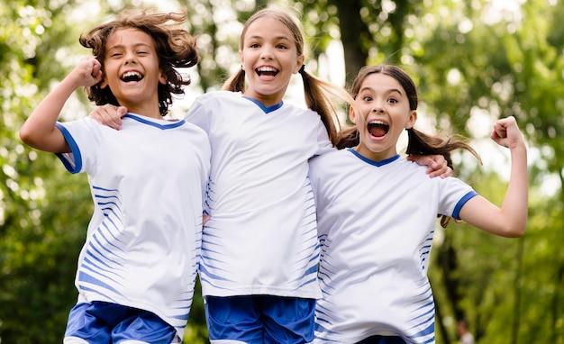 Crianças pulando depois de vencer uma partida de futebol