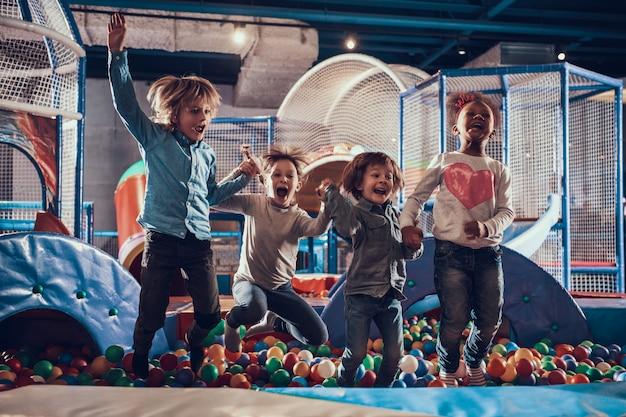 Crianças pulando na piscina cheia de bolas coloridas