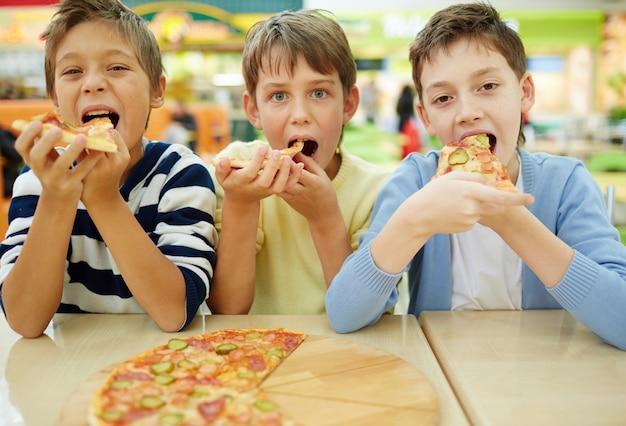 Crianças que apreciam a pizza
