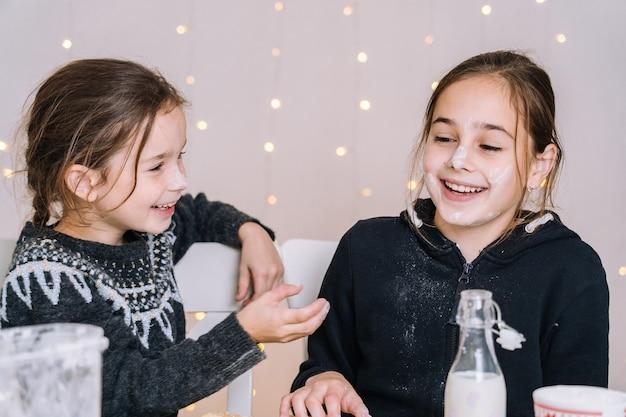 Crianças que cozem biscoitos do pão-de-espécie na cozinha da casa no dia de inverno. crianças brincando com farinha.