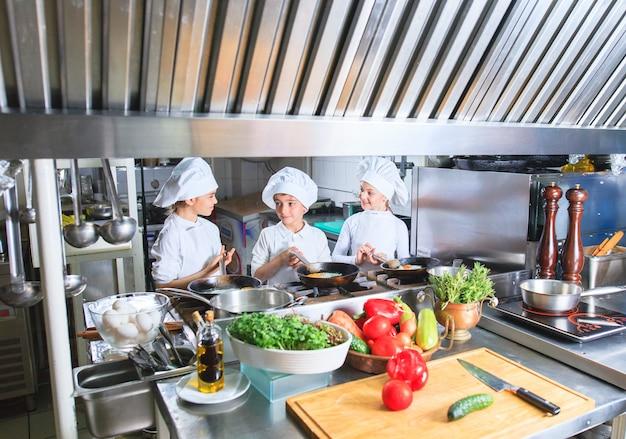 Crianças que cozinham o almoço em uma cozinha do restaurante.