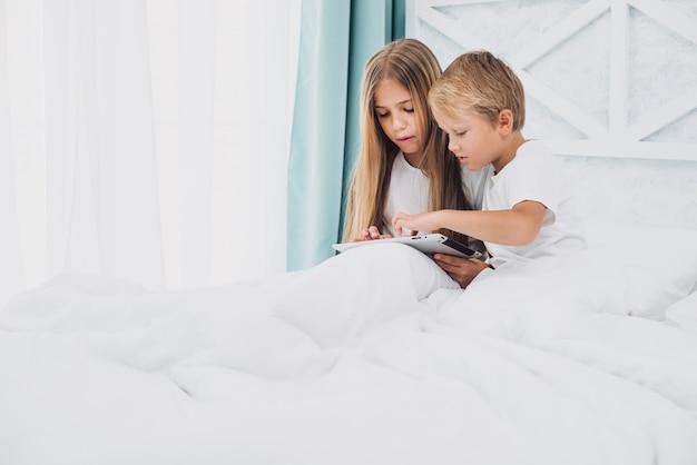 Crianças que ficam na cama enquanto brincam em um tablet