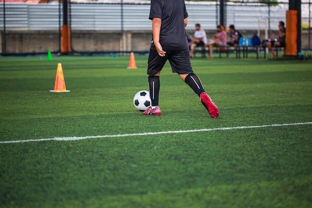 Crianças que jogam o cone de táticas de bola de futebol de controle no campo de grama com fundo de treinamento.