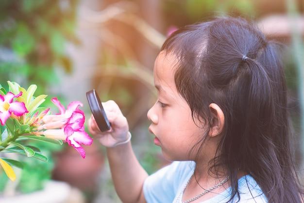 Crianças que olham flores com uma lupa.