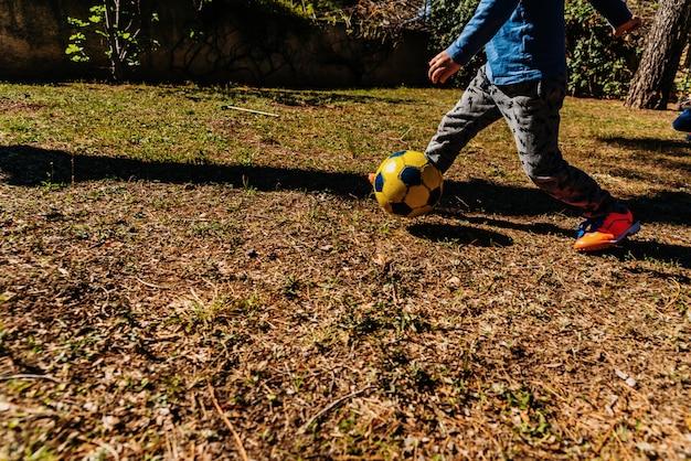Crianças que perseguem uma bola de futebol velha em um fósforo amigável no verão.
