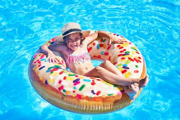 Crianças que sentam-se no anel inflável na piscina.
