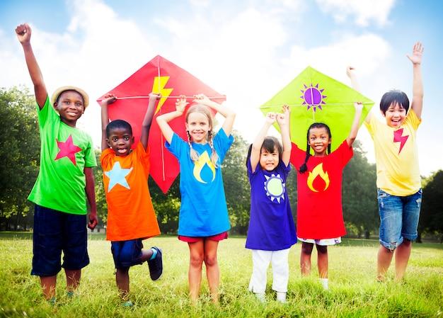 Crianças que voam o conceito brincalhão da amizade do papagaio
